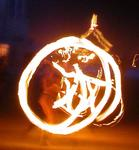 A fire-dancer swinging flames.