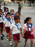 Children marching down the street in their school uniforms.