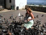 Cherie feeds the pigeons in the park.  *Photo by Stan.