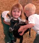 Ellie and Tanner give the goat a hug-ball.