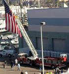 A huge American flag waved from the ladder of a firetruck.