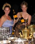 Cherie and Jean surrounded by champagne and trophies.