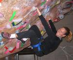 Cherie dangles upside down at an indoor rock climbing gym.  This is yoga for the adventurous!