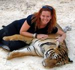 Cherie cuddles with a tiger at a forest monastery in Thailand.