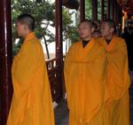 Preparing for the service, the monks enter in a parade of saffron.