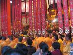 The room is packed with monks and Buddhist followers.