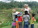 Children huddle around Margaret.  They are drawn by her blonde hair and tourist dollars.