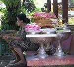 A woman sits next to the days offerings.
