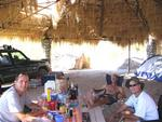 The guys hanging out under the shade of the palapa.