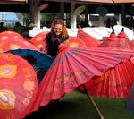 Cherie tucked in the colorful shade of hand-made bamboo parasols.