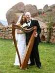 Kevin and Clara wed on October 21, 2005 in Red Rocks Park, Denver, Colorado.  True love is posing with your wife and a harp.