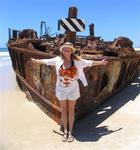 Cherie in front of a washed-up rusted ship wreck on Fraser Island, off the east coast of Australia.