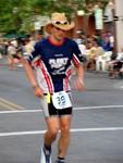 Crossing the finish line in a cowboy hat.