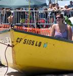 A female volunteer is ready to get pulled down the beach by a strongman.