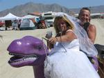 The happy couple rides off into the desert mirage on their purple dinosaur.