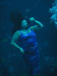 A former mermaid demonstrates drinking under water. *Photo by John Athanason