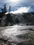 The air is warm and moist around the geothermal features.
